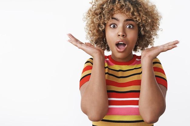 Omg auf keinen fall. porträt eines beeindruckten, sprachlosen, süßen afroamerikanischen mädchens, das erstaunliche nachrichten gelernt hat, die vor erstaunen die hände in der nähe des gesichts halten und die augen vor überraschung seitlich knallen lassen