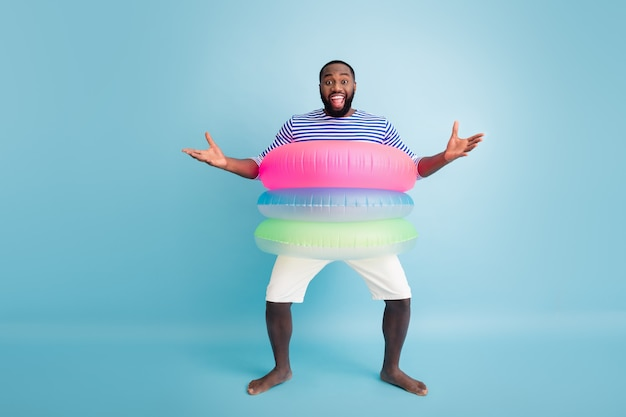 Omg, du bist es? foto in voller größe positiv verrückt barfuß afro-amerikaner genießen freizeit urlaub haben bojen wollen umarmung freund tragen gestreifte weste weiße shorts isoliert blaue farbe wand