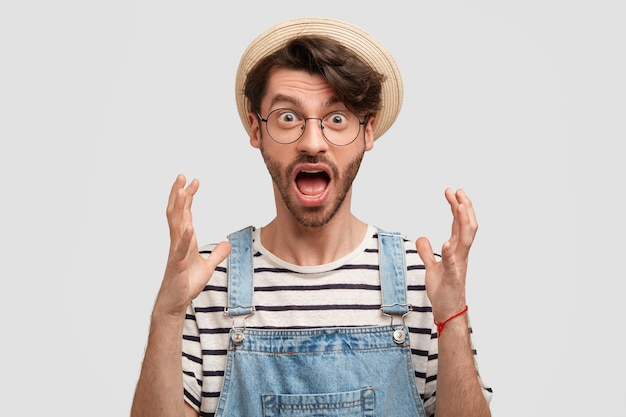 Omg, es ist schrecklich! emotionaler männlicher landarbeiter gestikuliert wütend, öffnet den mund weit und starrt mit verdorbenen augen, unzufrieden mit der saisonalen ernte, trägt ein lässiges landschaftsoutfit