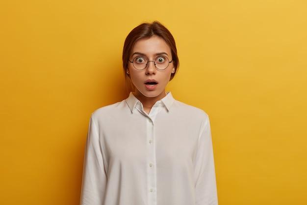 Omg, ich glaube nicht! schockierte emotionale frau trägt große optische brille und weißes hemd, reagiert auf überraschende nachrichten, hat weit geöffnete augen, isoliert über gelber wand. menschen- und emotionskonzept