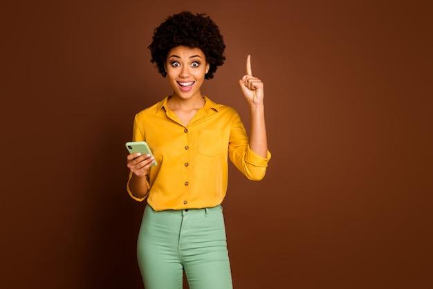 Omg ich weiß welcher text! aufgeregte verrückte afroamerikanische mädchen blogger verwenden smartphone-typ sms denken, bekommen unglaubliche idee heben finger hoch tragen gelb stilvolle grüne outfit isoliert braune farbe