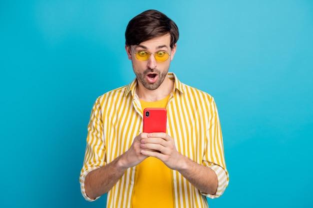 Omg quarantäne verlängerte grenzen geschlossen. erstaunter mann touristen verwenden smartphone beeindruckt soziale netzwerk-informationsreaktion tragen weiße gelbe kleidung isoliert blauer hintergrund