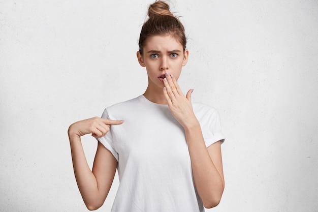 Omg, schau da! schockierte frau in der verwirrung bedeckt mund, trägt lässiges weißes t-shirt, zeigt mit dem vorderfinger auf leeren kopienraum, lokalisiert über weißem hintergrund. personen- und werbekonzept