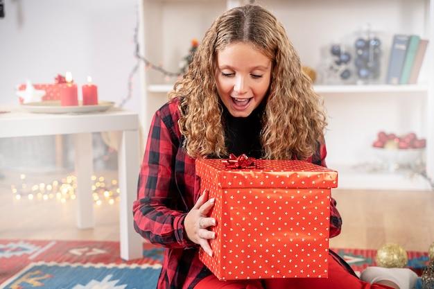 Omg. überraschtes mädchen kind rot geschenkverpackung überraschung genießen