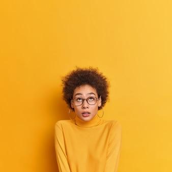 Omg unglaubliche sache oben. überraschtes, ziemlich lockiges afroamerikanisches mädchen, das oben konzentriert ist, hält den atem an und trägt eine transparente brille mit lässigem poloneck.