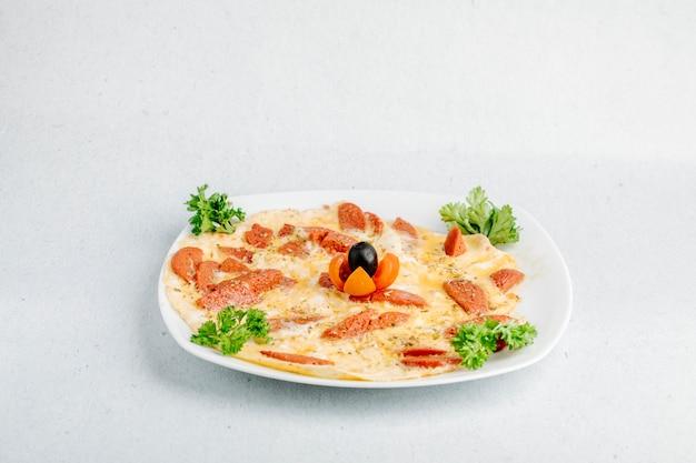 Omlette zum brunch mit peperoni, tomaten, schwarzen oliven und kräutern.