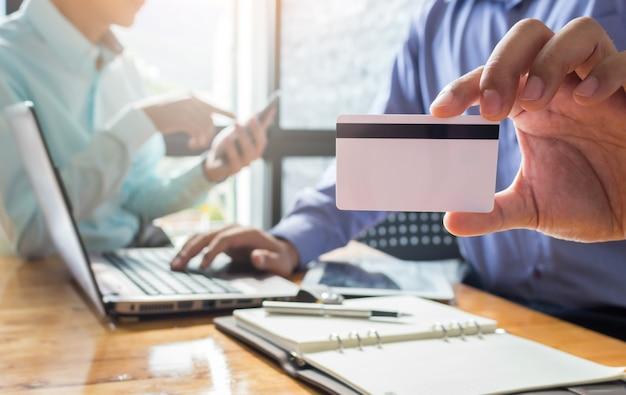 On-line-einkaufen, männerhände, die kreditkarte halten und laptop verwenden