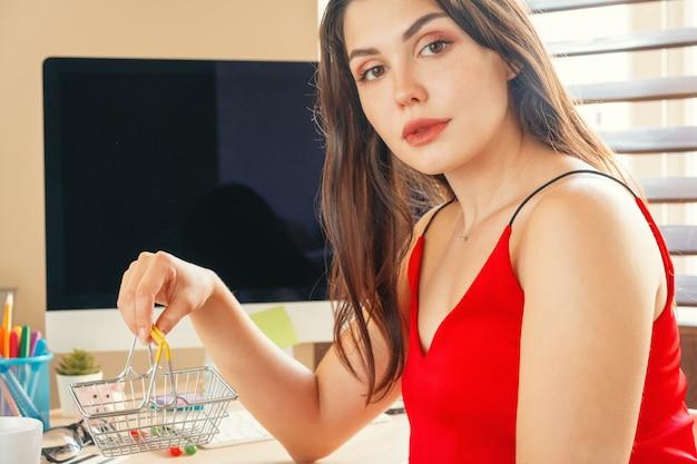 On-line-einkaufskonzept mit der frau, die am haupttisch mit computermonitor sitzt