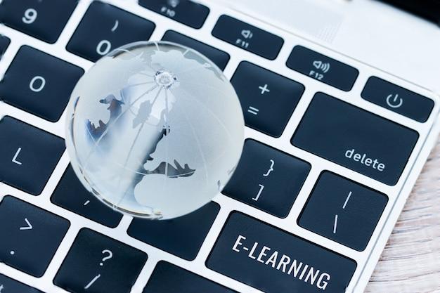 On-line-lernbildung durch technologiekonzept, wörter, die an e-learning sind, tragen schlüsselknöpfe des computerlaptops ein