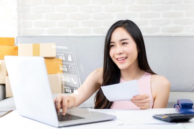 On-line-verkäufer der jungen frau, der an laptop-computer arbeitet
