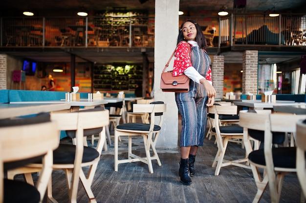Ð¡onfident junge afroamerikanerin in der schicken freizeitkleidung am café.