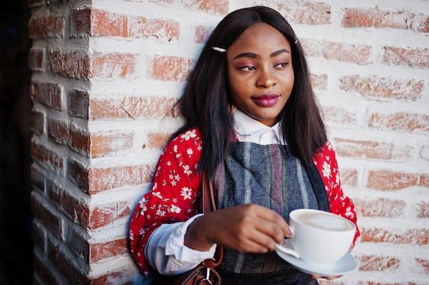Ð¡onfident junge afroamerikanische frau in der intelligenten freizeitkleidung im café mit tasse heißem getränk in der hand.