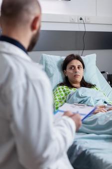 Onkologe arzt arzt bespricht medizinisches fachwissen, das krankheitssymptome für kranke frau erklärt