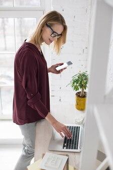 Online-agenda. angenehme glückliche geschäftsfrau, die laptop und telefon hält