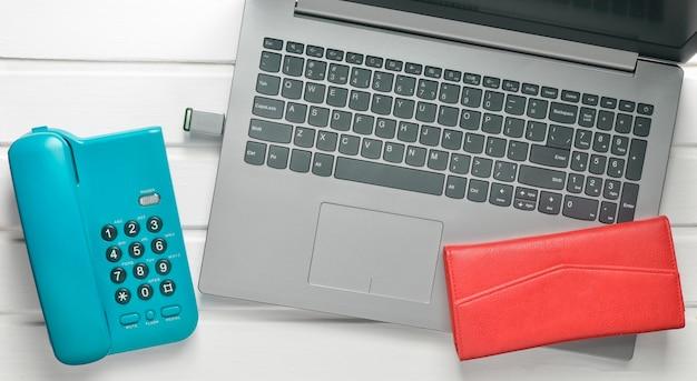 Online-arbeit, freiberufliches konzept. bürotelefon, laptop, flash-laufwerk, brieftasche auf einem weißen holztisch. draufsicht.