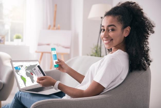 Online banking. freudige nette frau, die eine kreditkarte hält, während sie eine bank-app auf ihrem smartphone benutzt