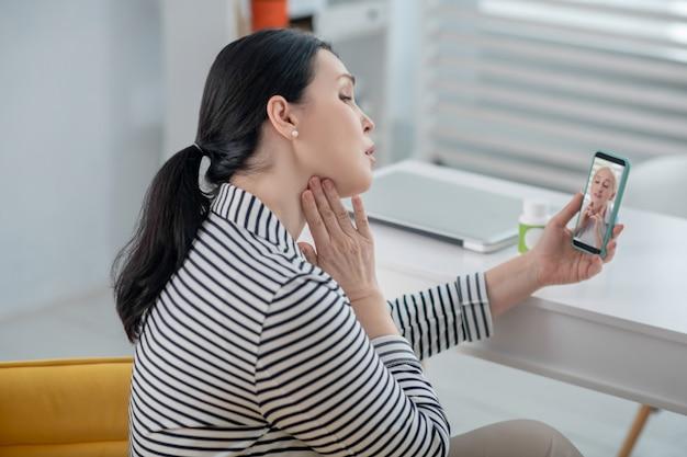 Online-beratung. frau, die in einem stuhl mit einem smartphone in der hand sitzt und gesundheitsberatung mit einem arzt online hat.