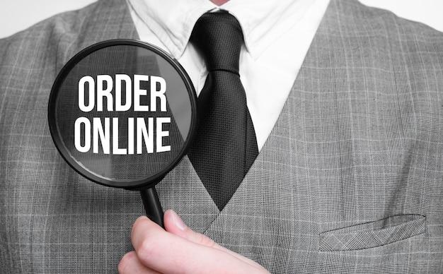 Online bestellen. bildungskonzept. geschäftsmannhände mit lupe.