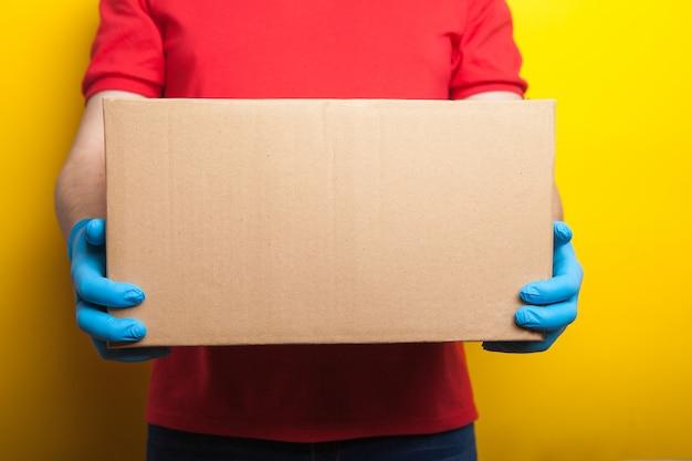 Online-bestellung und lieferung. ein mann in roter uniform und medizinischen gummihandschuhen hält eine schachtel in leuchtendem gelb. lebensmittellieferung während der quarantänezeit des coronavirus.