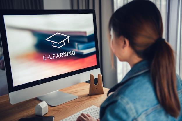 Online-bildung, e-learning. junge frau sitzt am tisch und arbeitet am computermonitor mit inschrift auf dem bildschirm