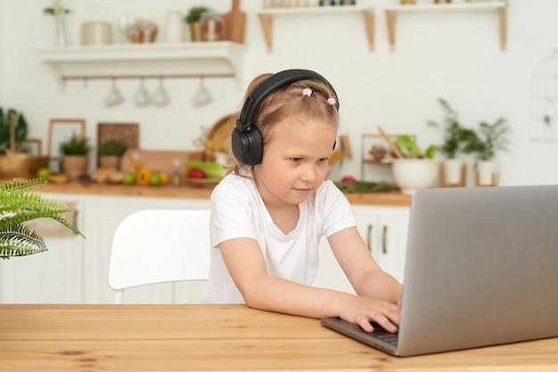 Online-bildung für kinder. schulmädchen, das online-unterricht per videokonferenz per laptop-video-chat von zu hause aus ansieht. kleines mädchen spielt spiele mit kopfhörern, die in der küche sitzen.