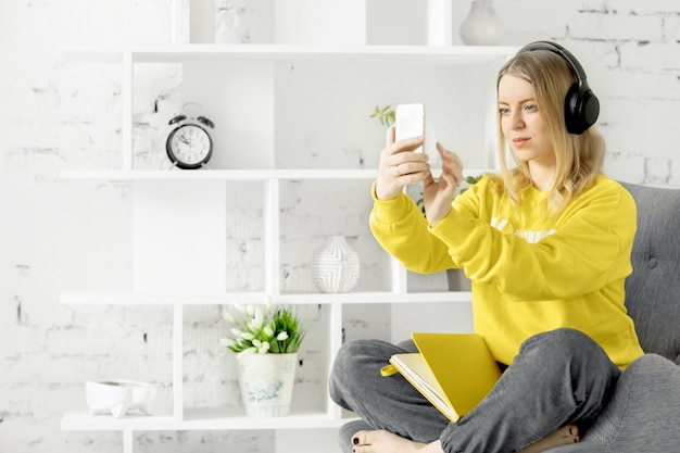 Online-bildung, vlog, video-blogging-konzept. frau in den kopfhörern in der gelben bluse sitzt auf grauer couch verwenden smartphone, um musik zu hören