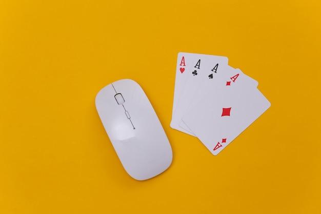 Online casino. pc-maus und vier asse auf gelbem hintergrund. ansicht von oben