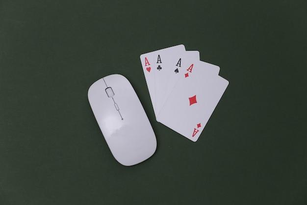 Online casino. pc-maus und vier asse auf grünem hintergrund. ansicht von oben
