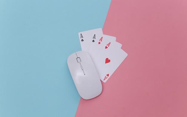 Online casino. pc-maus und vier asse auf rosa blauem hintergrund. ansicht von oben