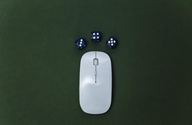 Online casino. pc-maus und würfel auf grünem hintergrund. ansicht von oben