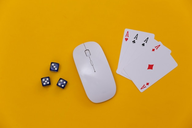 Online casino. pc-maus, würfel und vier asse auf gelbem hintergrund. ansicht von oben