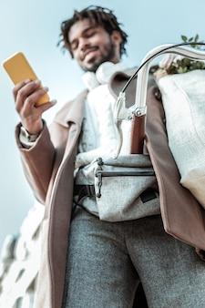 Online chat. fröhliche brünette, die ein lächeln auf seinem gesicht behält, während sie auf sein telefon schaut