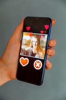 Online-dating-app im smartphone. mann, der foto der schönen frau betrachtet.
