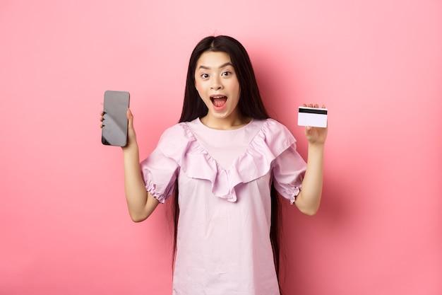 Online einkaufen. aufgeregte asiatische frau, die plastikkreditkarte mit leerem smartphonebildschirm, werbendem internet-shop zeigt, der auf rosa hintergrund steht.