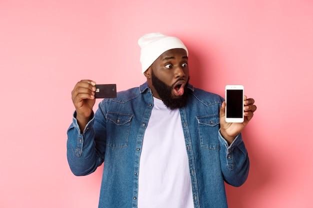 Online einkaufen. beeindruckt und überrascht schwarzer mann, der kreditkarte zeigt, auf den smartphone-bildschirm starrt, app demonstriert und über rosafarbenem hintergrund steht.