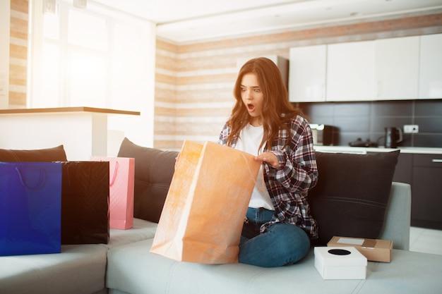 Online einkaufen, bestellte eine junge frau lieferung nach hause. jetzt sitzt sie auf der couch und packt ihre neuanschaffungen aus.