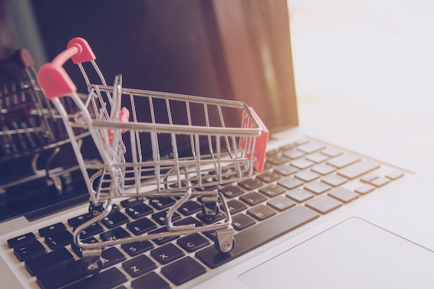 Online einkaufen. einkaufswagenlogo auf einer laptoptastatur