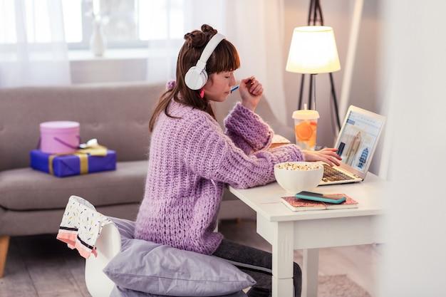 Online einkaufen. ernstes schulmädchen, das zu hause ist und freizeit vor dem computer verbringt