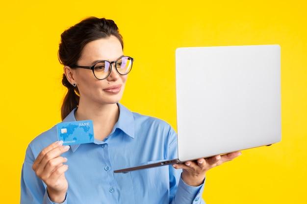 Online einkaufen. frau, die laptop hält und dinge wählt, um auf gelb zu kaufen