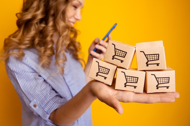 Online einkaufen. frau, die papierkästen hält und telefon verwendet.