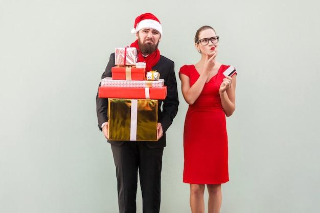 Online einkaufen. frau im roten kleid, die kreditkarte hält und denkt, was sie sonst noch kaufen soll. unglücklicher mann, der viele kästen hält und kamera betrachtet isolierte aufnahme auf grauem hintergrund