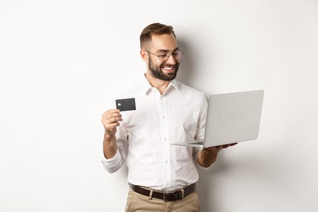 Online einkaufen. hübscher geschäftsmann, der kreditkarte hält und laptop verwendet, internet-zahlung macht, über weißem hintergrund stehend.