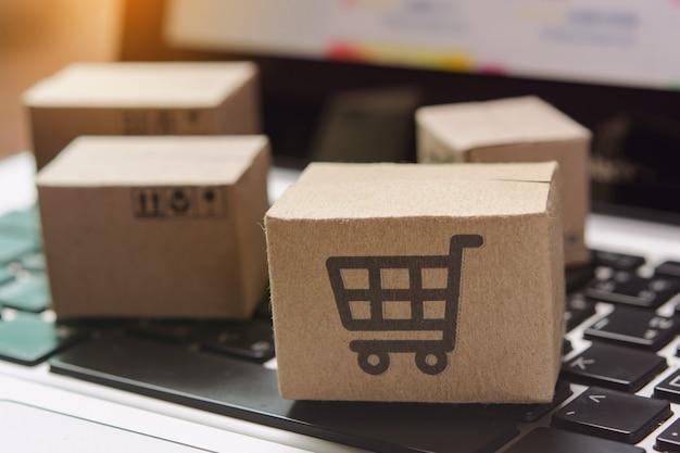 Online einkaufen. karton mit einkaufswagen-logo auf der laptop-tastatur. einkaufsservice im online-web. bietet lieferung nach hause