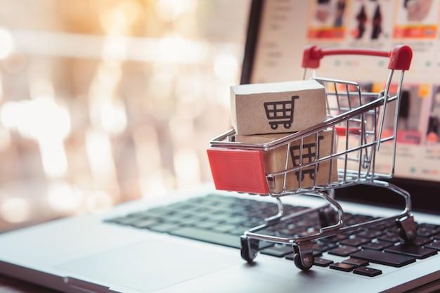 Online einkaufen. karton mit einkaufswagen-logo in einem trolley auf der laptop-tastatur. einkaufsservice im online-web. bietet lieferung nach hause