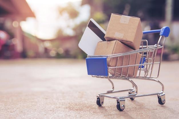 Online einkaufen. kartons oder papierkästen und kreditkarte im warenkorb auf konkretem boden.