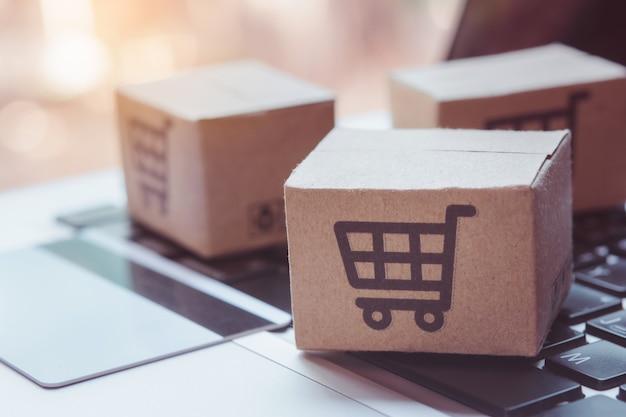 Online einkaufen. kreditkarte und karton mit einkaufswagen-logo auf der laptop-tastatur. einkaufsservice im online-web. bietet lieferung nach hause