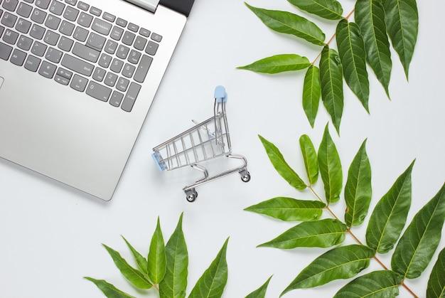 Online einkaufen. laptop, einkaufswagen auf weißem hintergrund mit grünen blättern. konzept der einheit mit der natur. öko-stillleben. draufsicht