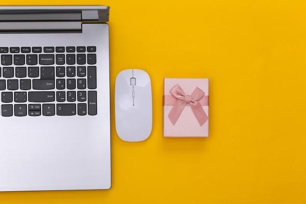 Online einkaufen. laptop mit pc-maus, geschenkbox auf gelbem hintergrund. ansicht von oben.
