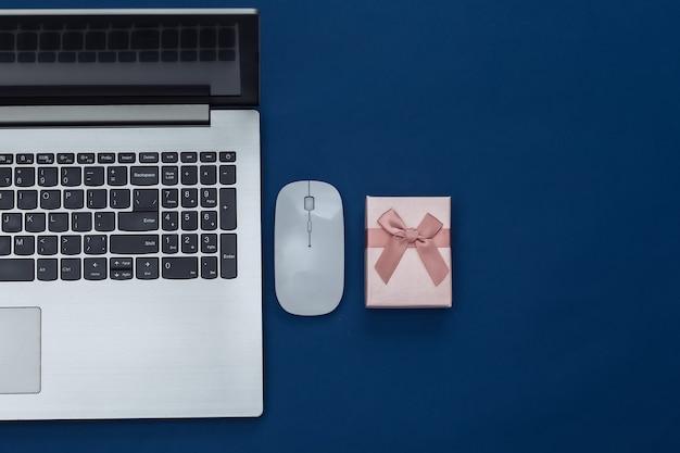 Online einkaufen. laptop mit pc-maus, geschenkbox auf klassischem blauem hintergrund. farbe 2020. ansicht von oben.