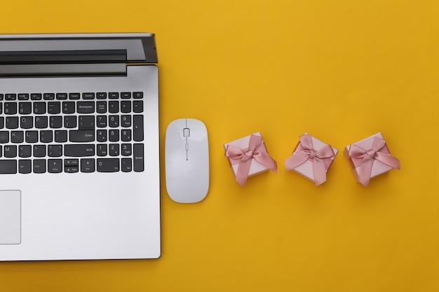 Online einkaufen. laptop mit pc-maus, geschenkboxen auf gelbem hintergrund. ansicht von oben.